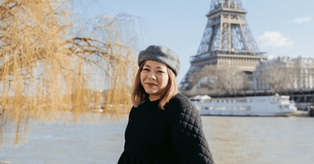 Christy Innouvong of Courageous Kitchen in Paris posing with the Eiffel Tower