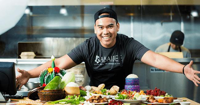 Boi Singharaj posing with Lao food at his restaurant Sabaidee: Lao & Thai Street Food in Texas
