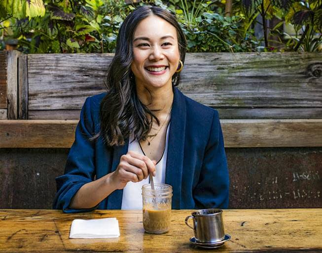Sahra Nguyen smiling with her own coffee