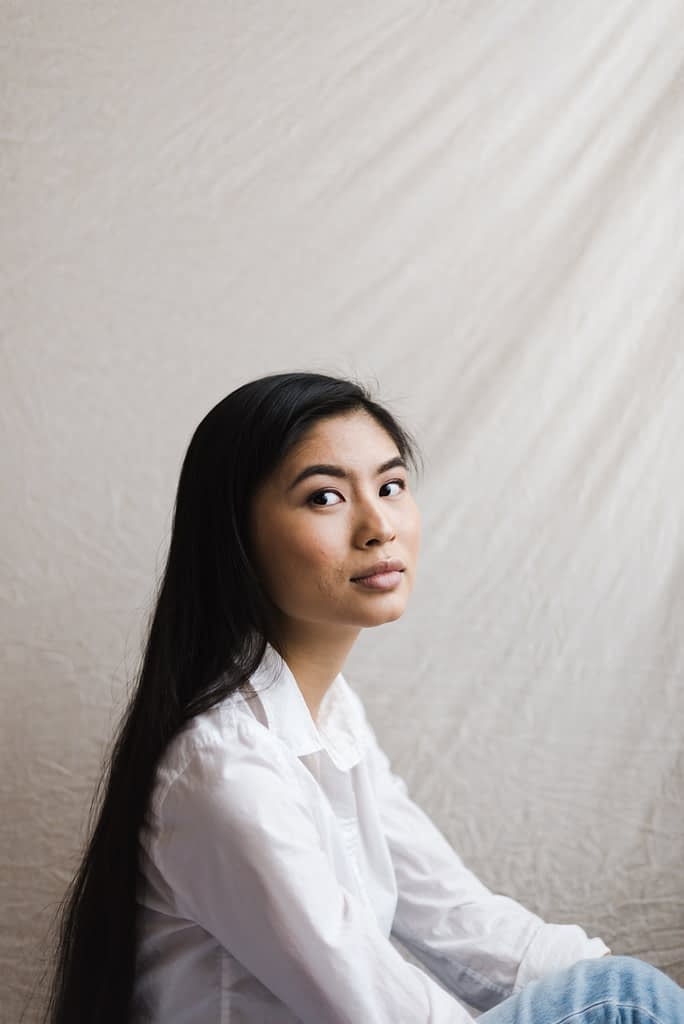 Asian American woman with long black hair wearing white collared shirt and denim sitting on the floor