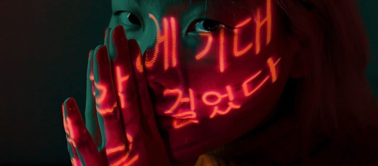 woman wearing a yellow sweater in neon light with Korean characters