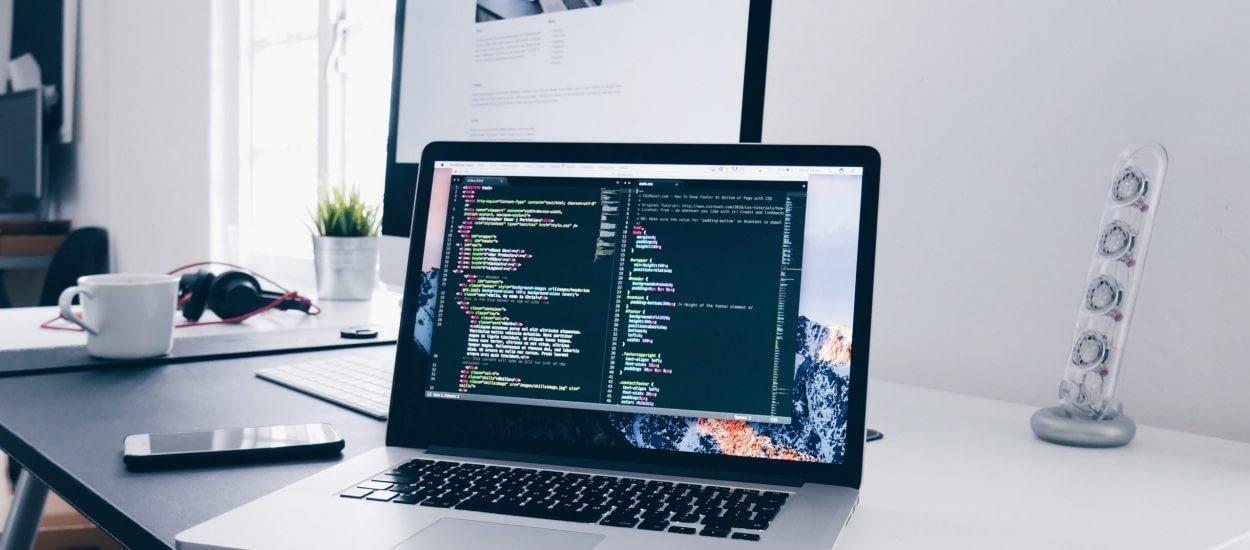 Laptop on desk displaying code
