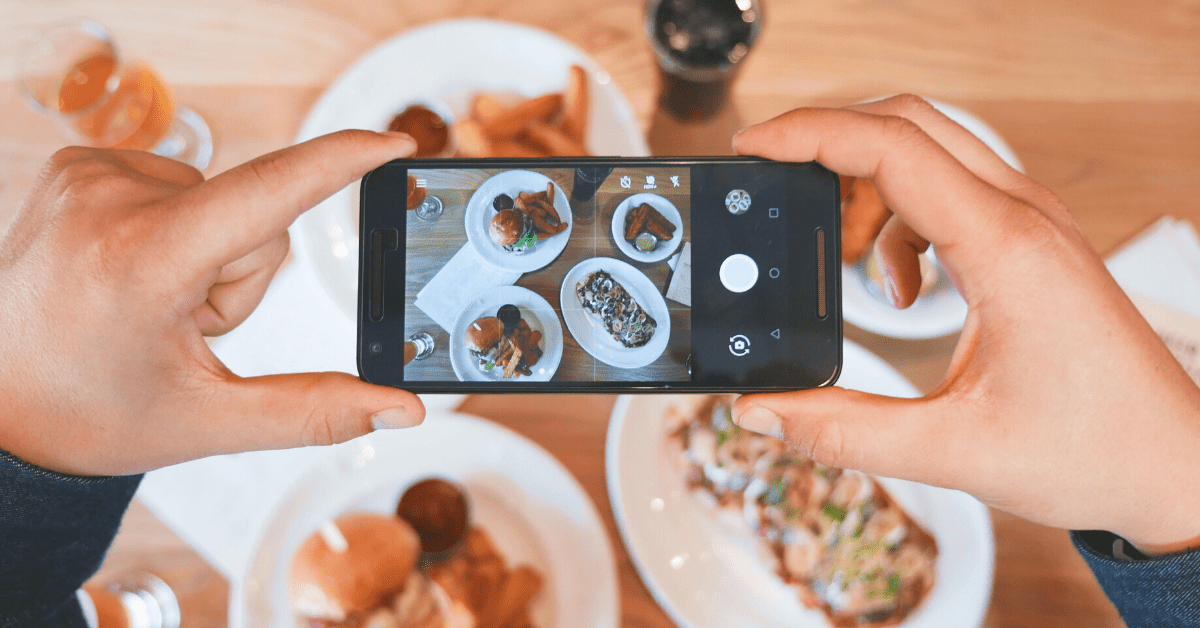 someone taking an overhead photo with an iphone of food on a table