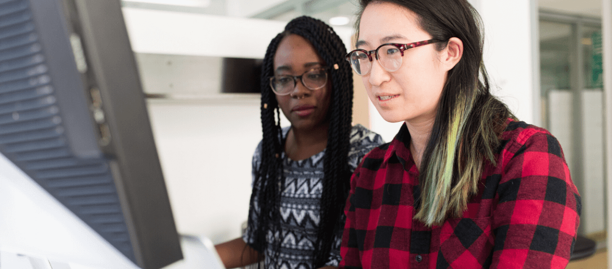 Asian American and African American women working together at a computer