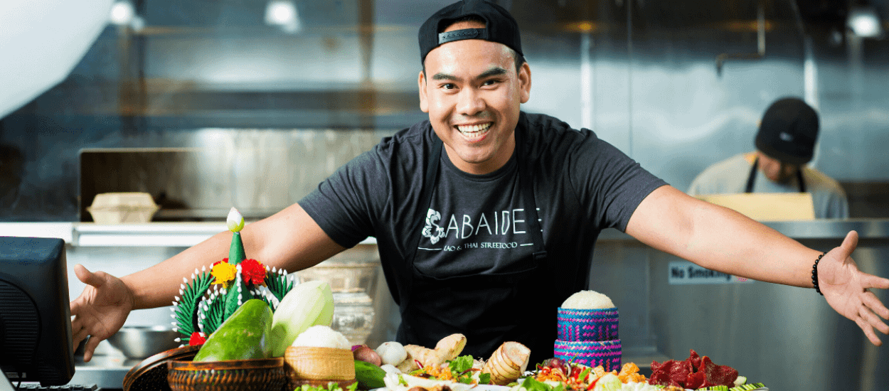 Boi Singharaj posing with Lao food at his restaurant Sabaidee: Lao & Thai Street Food in Texas