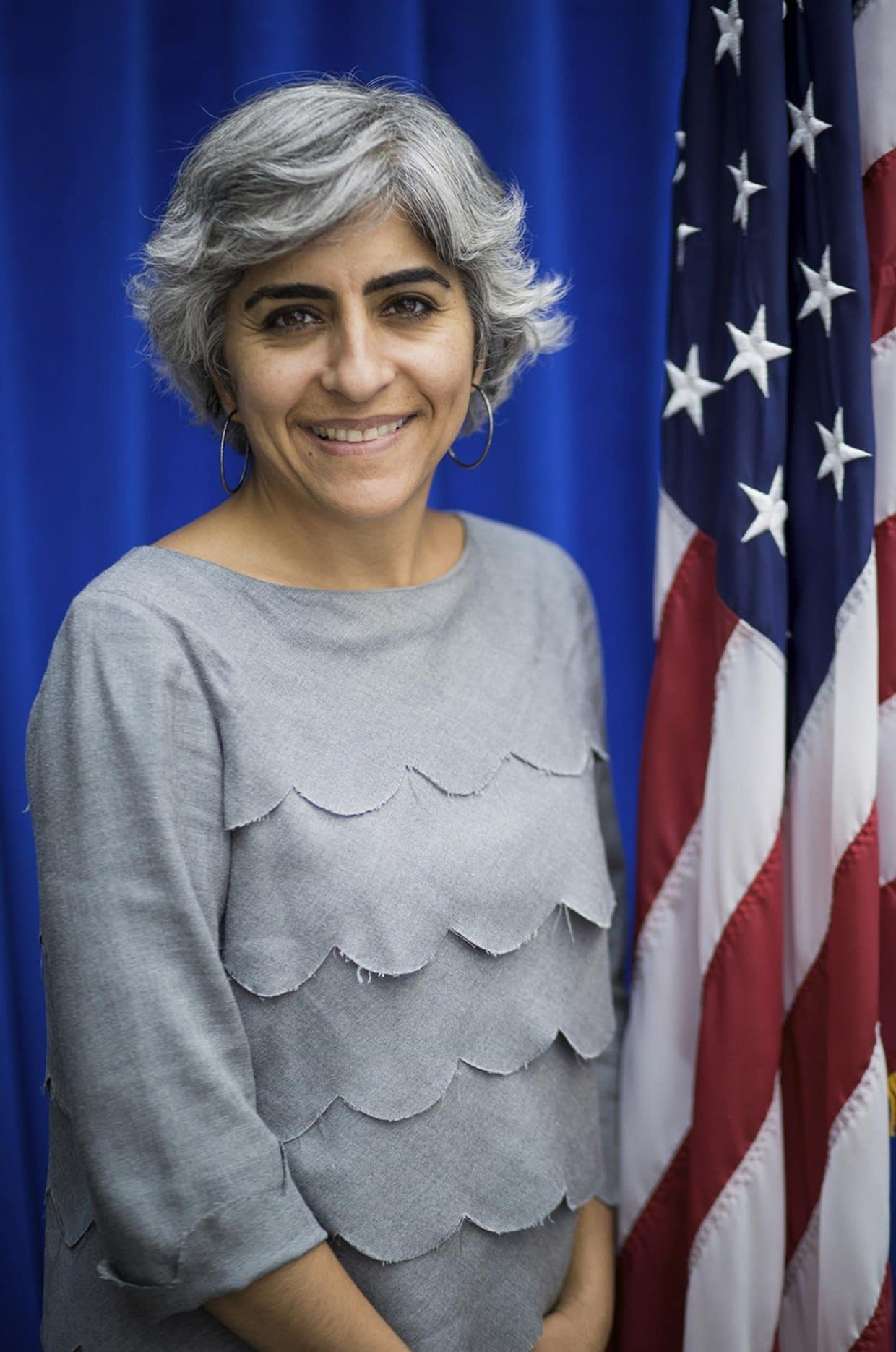 Professional photo of Kiran Ahuja smiling with the American flag