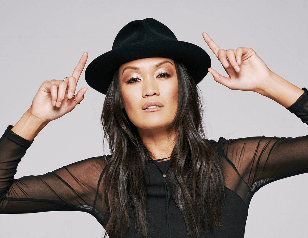Southeast Asian American actress Sydney Viengluang wearing a fedora and black lace shirt